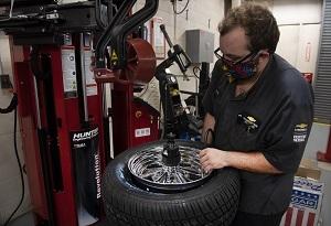 A man wearing a mechanic uniform and black masks handles a tire